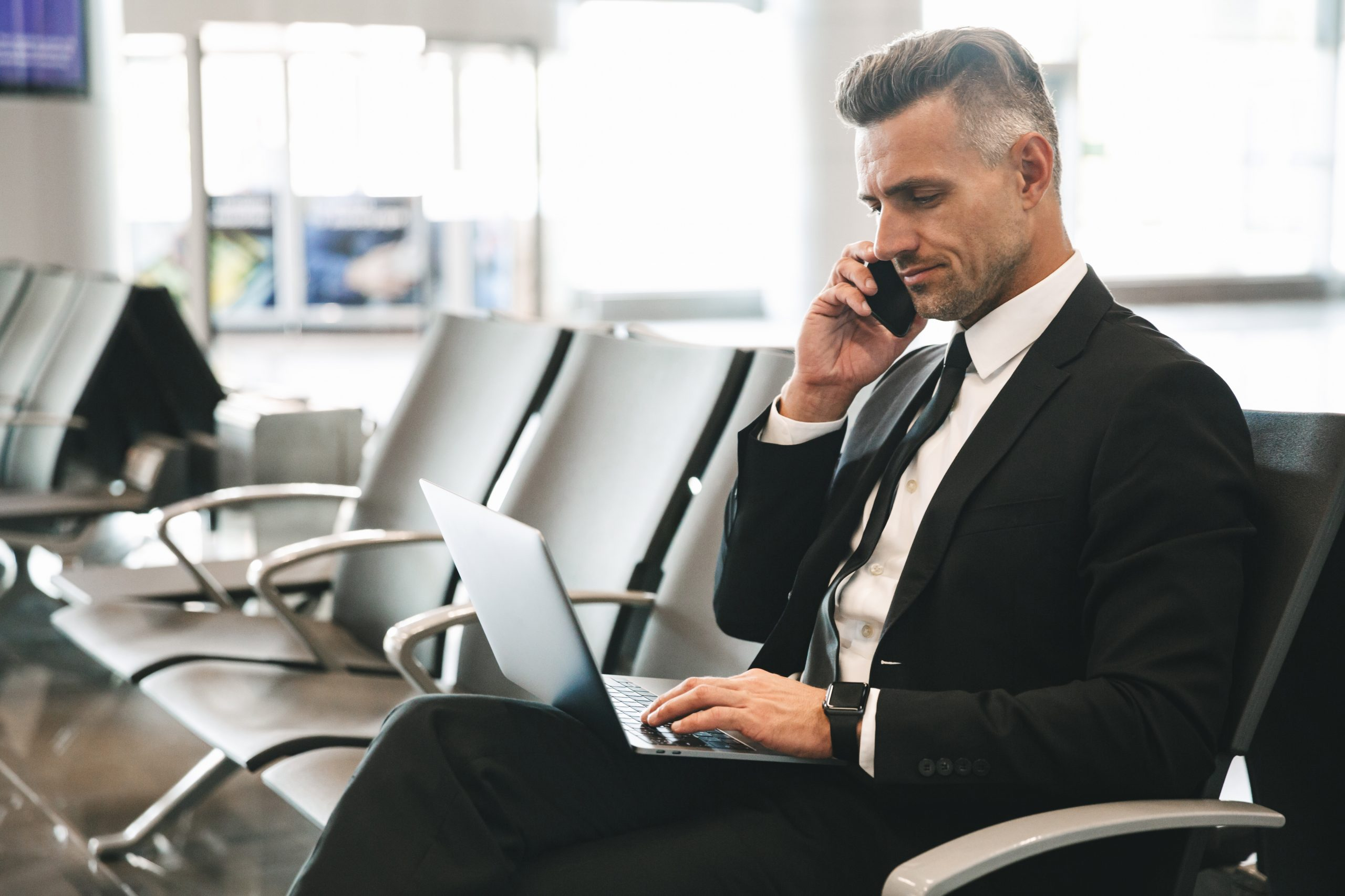 Handsome mature businessman talking on mobile phone while sitting at the airport lobby with laptop computer